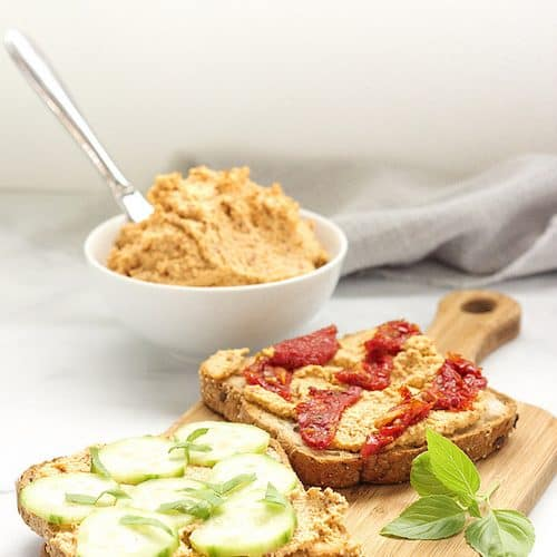 bowl of vegan almond cheese used as a topping on toast with vegetables