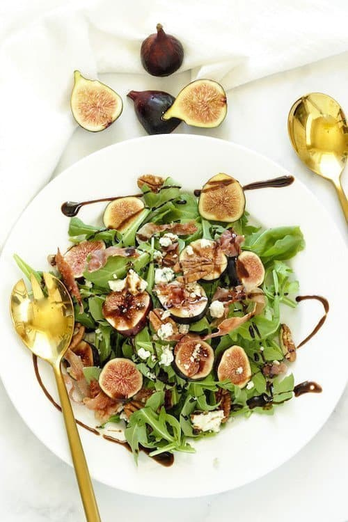 fig and arugula salad with blue cheese and prosciutto served on a plate