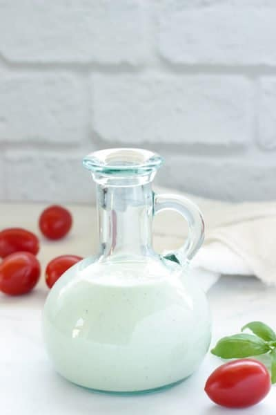 salad dressing bottle full of homemade blue cheese dressing surrounded by cherry tomatoes