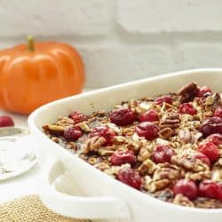 White casserole dish with pumpkin gingerbread baked oatmeal and a pumpkin in the background