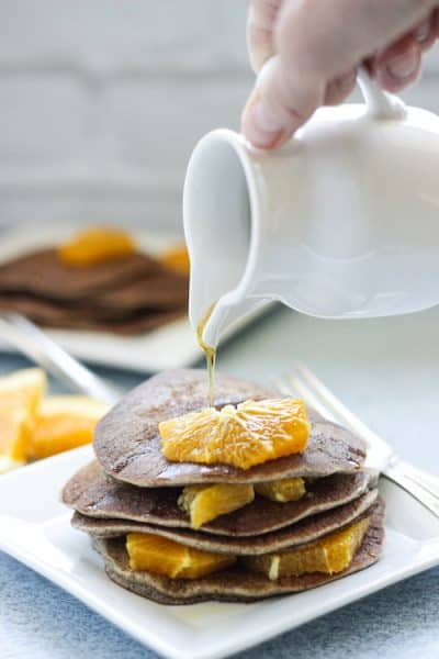 a plate of buckwheat pancakes with orange segments on top and a pitcher of syrup pouring over