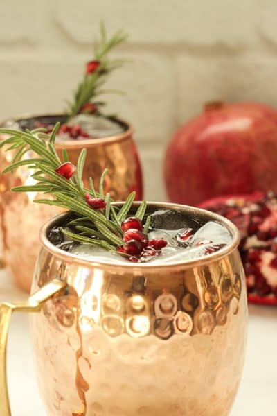 2 copper mugs with pomegranate mule cocktails garnished with a rosemary sprig and pomegranate arils