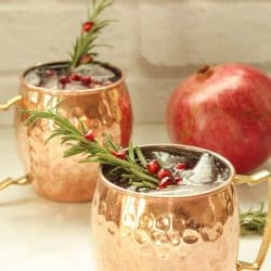 2 copper mugs with pomegranate mule drinks garnished with rosemary sprig and pomegranate arils