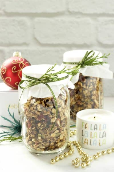 2 mason jars with granola surrounded by christmas ornaments