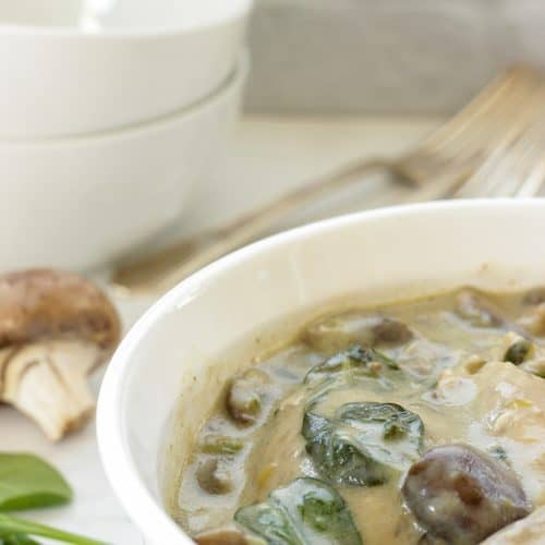 Creamy braised chicken with mushrooms and spinach in a white casserole dish with two white bowls in the background