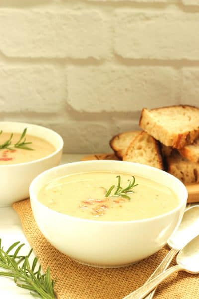 Creamy white bean fennel soup in a white bowl garnished with fresh rosemary