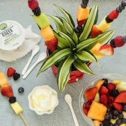 Fruit skewer and plant arrangement with a white bowl of fruit dip