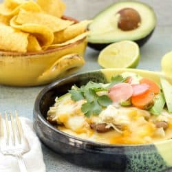 A casserole dish with Green Chicken Enchilada Pie a bowl of tortilla chips, half and avocado and lime in the background