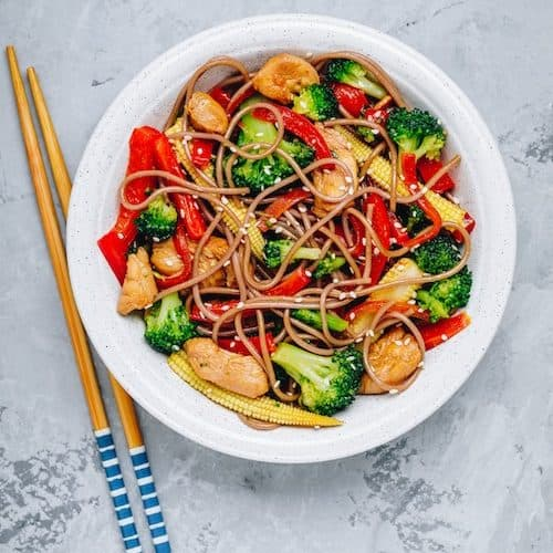 white plate with stir fried chicken and vegetables