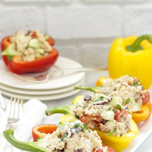 Red, yellow, and orange sweet peppers stuffed with sprouted brown rice tuna salad on a white plate