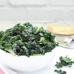 white bowl of kale chips dusted with Parmesan cheese