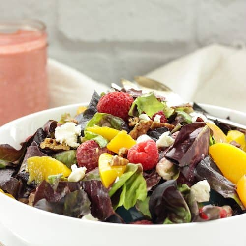 white bowl of salad topped with peaches and raspberries