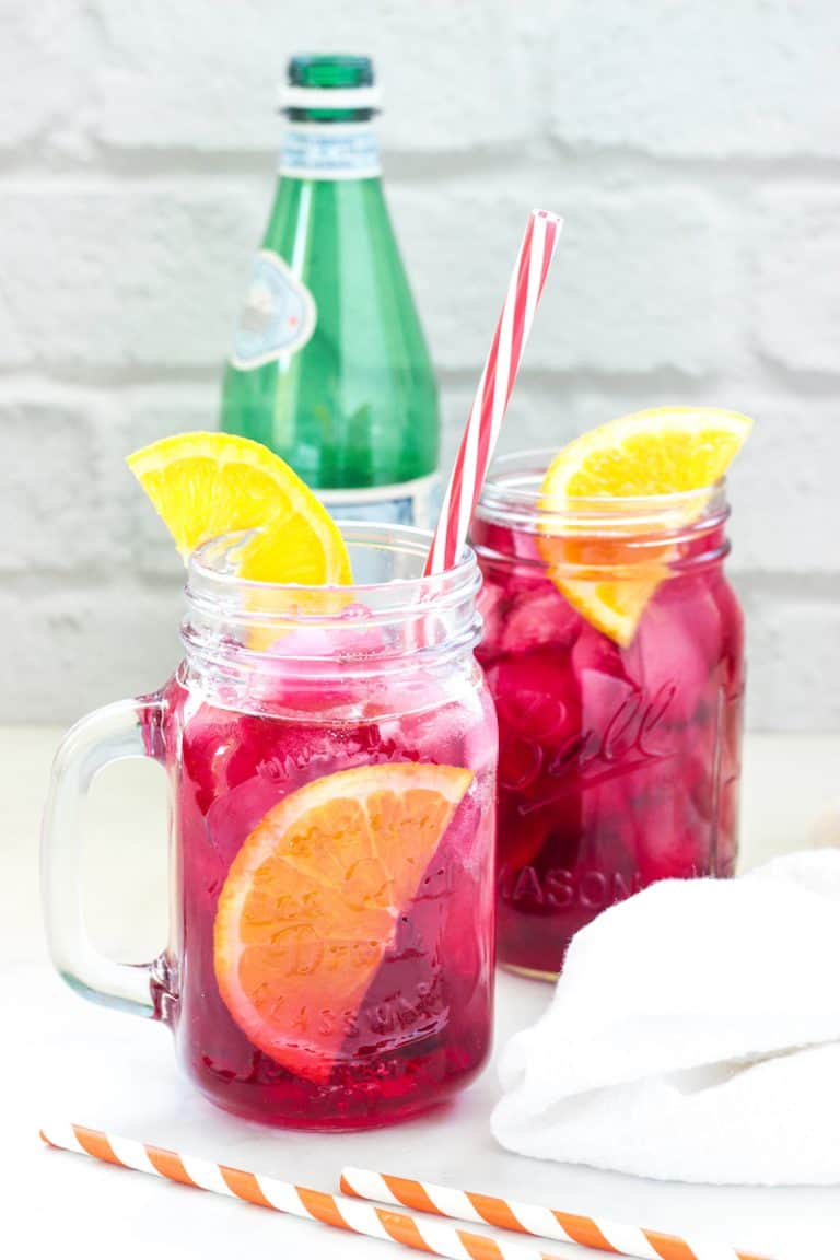 2 glasses of red hibiscus iced tea with orange slices