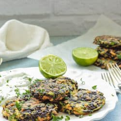 white plate with 3 vegetable fritters and a half of a lime