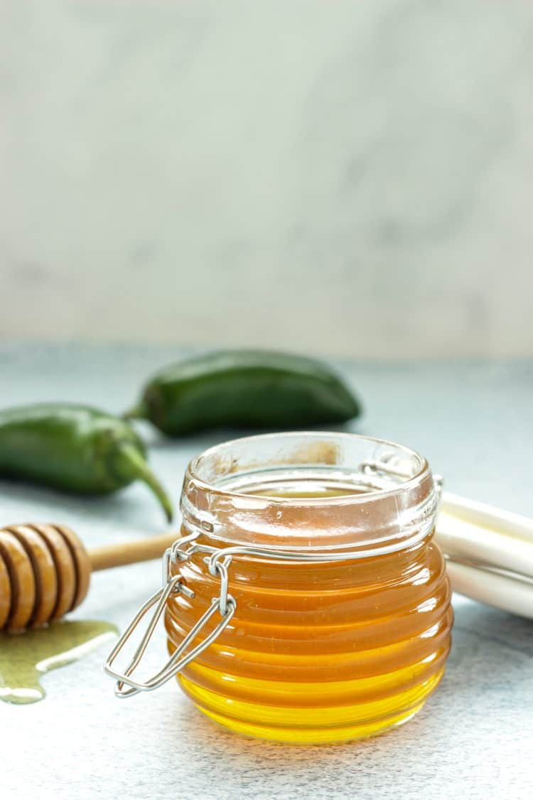 small jar of honey with 2 jalapeno peppers